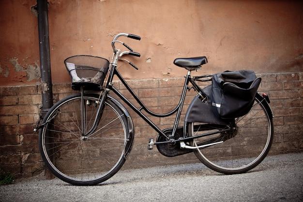 Vecchia bicicletta retrò con cesto contro la parete del grunge
