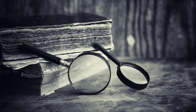 Un vecchio libro retrò sul tavolo. un'enciclopedia del passato su un vecchio piano di lavoro in legno. un vecchio libro dei bibiotici, un foglio, una costituzione, la bibbia.