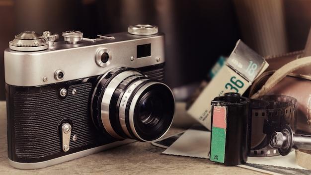 Vecchia macchina fotografica retrò, cassetta, rullino fotografico e foto sul tavolo di legno. immagine stilizzata dell'annata.