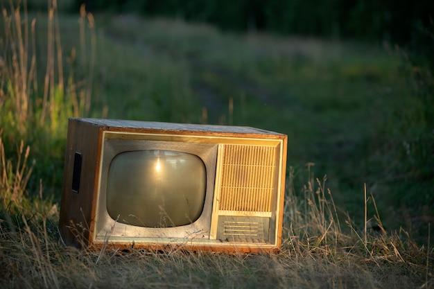 Vecchio televisore retrò su una strada di campo contro uno sfondo di grano sotto i raggi del sole al tramonto