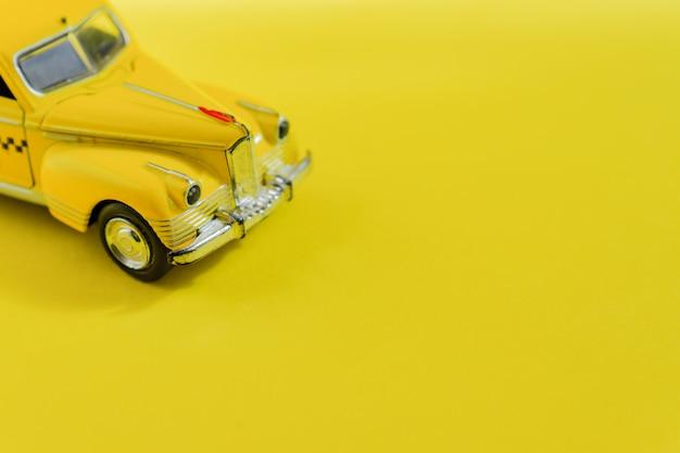 Vecchio retro taxi giallo dell'automobile del giocattolo su giallo