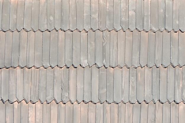 Il vecchio tetto è fatto di tegole di legno. struttura. avvicinamento