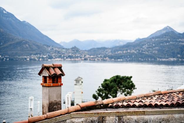 Un vecchio camino sul tetto con vista sulle montagne d'acqua e sull'insediamento