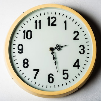 Vecchio orologio rotondo della stazione sulla parete bianca