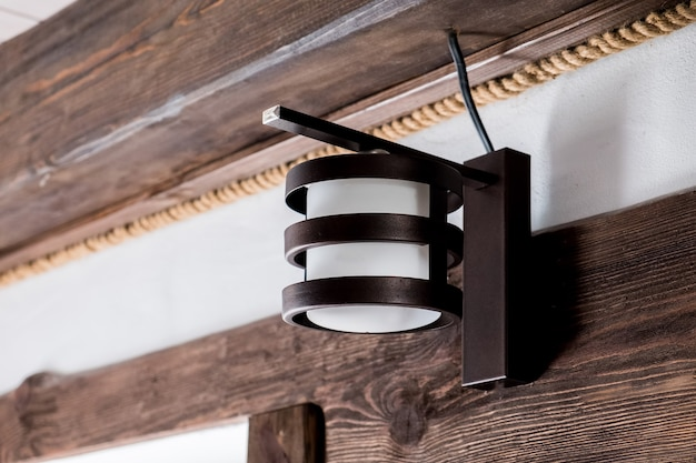 Vecchia lampada da parete rotonda su tavola di legno