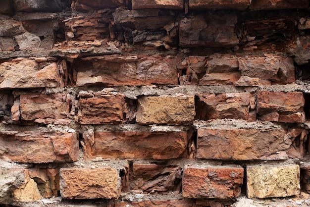 Vecchio muro di mattoni arancione rovinato con crepe. danneggiato antico mattone texture di sfondo da vicino