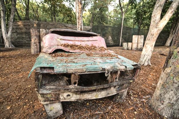 Una vecchia macchina arrugginita e abbandonata in una base di paintball dietro la quale si nascondono i giocatori eccitati dal gioco