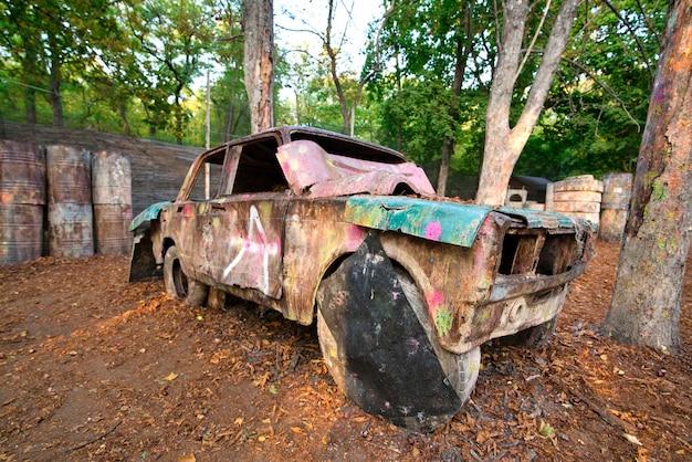 Una vecchia automobile arrugginita e abbandonata in una base di paintball