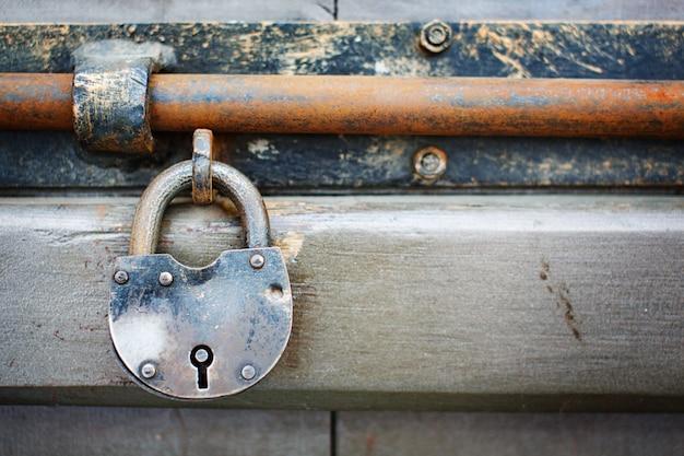 Vecchio lucchetto invecchiato arrugginito sulla porta