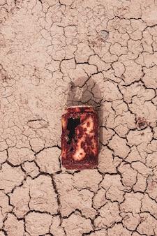 Vecchia lattina arrugginita sul terreno del dessert riscaldamento globale