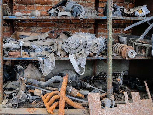 Vecchie parti di auto arrugginite impilate su uno scaffale