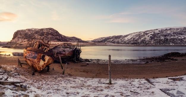Un vecchio peschereccio arrugginito abbandonato da una tempesta sulla riva. cimitero di navi, antico villaggio di pescatori sulla riva del mare di barents, la penisola di kola, teriberka, russia.