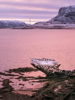 Un vecchio peschereccio arrugginito abbandonato da una tempesta sulla riva