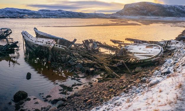 Un vecchio peschereccio arrugginito abbandonato da una tempesta sulla riva Foto Premium