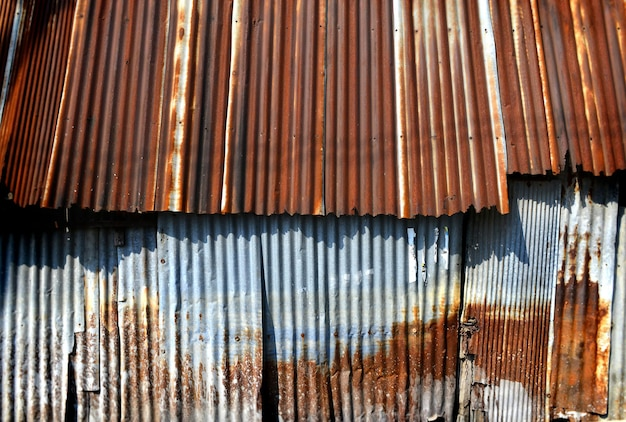 Vecchio e arrugginito galvanizzato su una povera struttura della casa e colore del passato