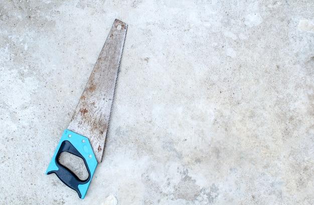 Vecchia sega a mano arrugginita su un pavimento di cemento