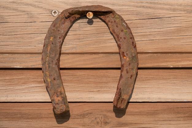 Vecchio ferro di cavallo arrugginito sul bordo di legno dell'annata
