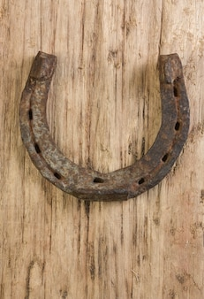 Vecchio ferro di cavallo arrugginito su uno sfondo di legno