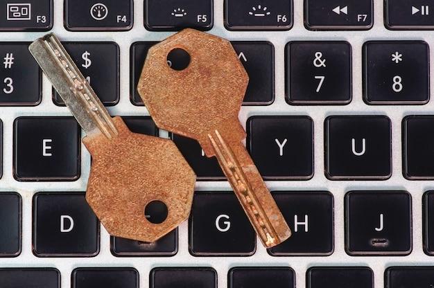 Chiavi vecchie e arrugginite sulla tastiera del computer portatile, sulla sicurezza del computer e sul concetto di password