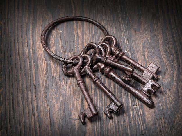 Vecchie chiavi arrugginite su fondo di legno