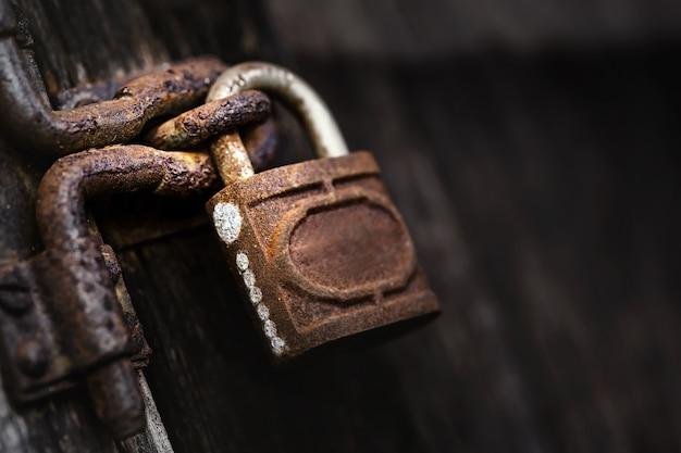 Lucchetto vecchio e arrugginito sulla porta di legno.