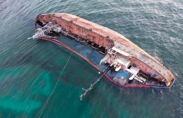 Una vecchia petroliera arrugginita giace sul mare