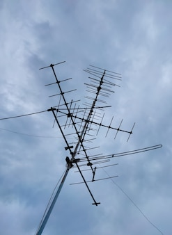 Vecchia antenna tv arrugginita contrasta con il cielo e le nuvole di pioggia.