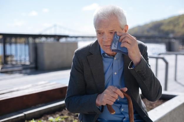 Vecchio triste uomo ordinato che si strofina via le lacrime mentre è seduto sulla panchina e ricorda sua moglie