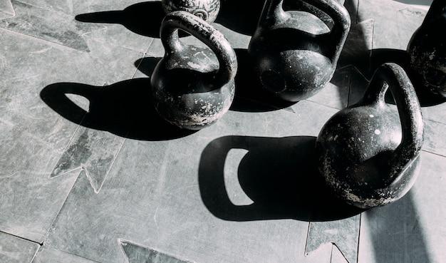 Vecchi manubri antigraffio su una superficie di gomma in palestra alla luce del sole.