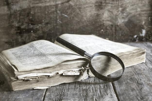 Vecchio effetto graffiato sulla lente d'ingrandimento della foto e sul vecchio libro