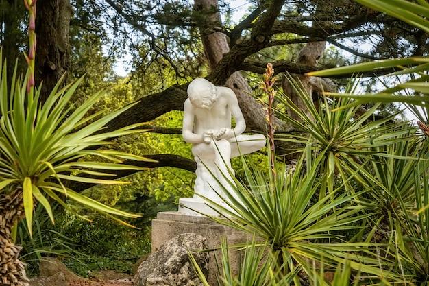 Una vecchia scultura di un ragazzo che si prende una scheggia dalla gamba nel giardino botanico nikitsky