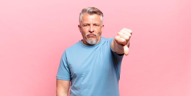 Il vecchio uomo anziano si sente arrabbiato, arrabbiato, infastidito, deluso o dispiaciuto, mostrando il pollice verso il basso con uno sguardo serio