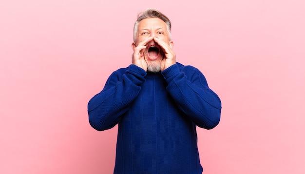 Il vecchio uomo anziano si sente felice, eccitato e positivo, emette un grande grido con le mani vicino alla bocca, chiamando