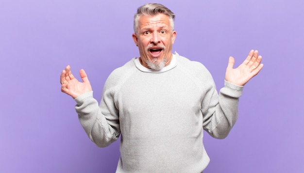 Il vecchio uomo anziano si sente felice, eccitato, sorpreso o scioccato, sorridente e stupito per qualcosa di incredibile