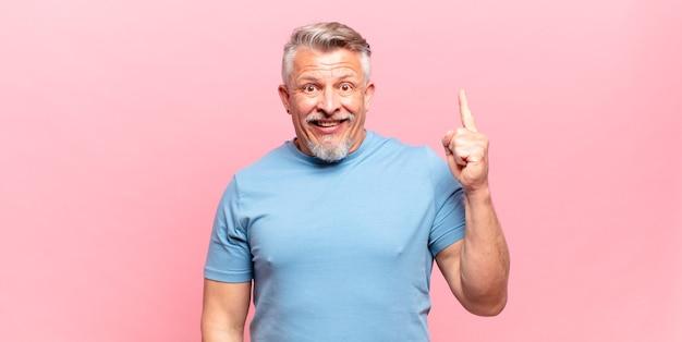 Il vecchio uomo anziano si sente un genio felice ed eccitato dopo aver realizzato un'idea, alzando allegramente il dito, eureka!