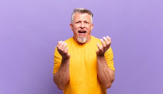 Il vecchio uomo anziano sembra disperato e frustrato, stressato, infelice e infastidito, urlando e urlando