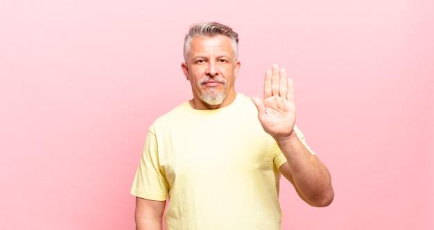Vecchio uomo anziano che sembra serio, severo, dispiaciuto e arrabbiato che mostra il palmo aperto che fa un gesto di arresto