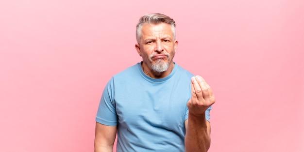 Il vecchio uomo anziano che fa un gesto di denaro o di denaro, dicendoti di pagare i tuoi debiti!