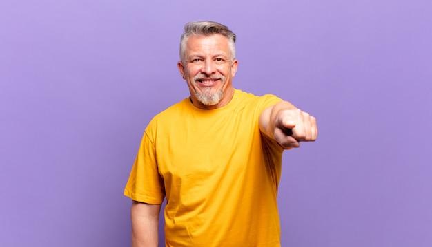 Il vecchio uomo anziano che punta alla telecamera con un sorriso soddisfatto, fiducioso e amichevole, scegliendo te