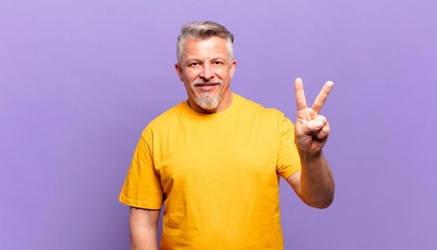 Vecchio uomo anziano sorridente e dall'aspetto amichevole, mostrando il numero due o il secondo con la mano in avanti, conto alla rovescia