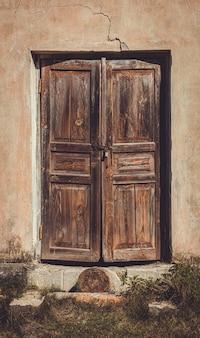 Vecchie porte di legno sbiadite malandate in una casa abbandonata