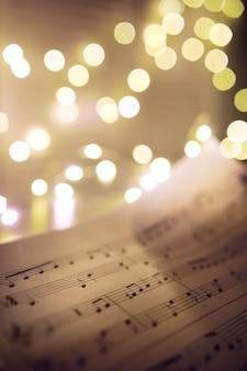 Vecchio foglio con note musicali di natale come sfondo contro luci sfocate. concetto di musica di natale