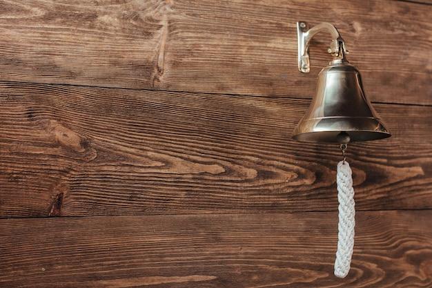 Vecchia campana della nave su una parete in legno