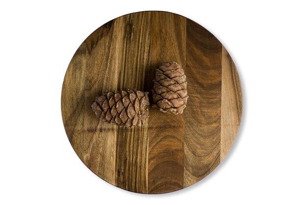 Un vecchio tagliere di legno tagliuzzato con coni di cedro, isolato su una superficie bianca. close-up di texture, vista dall'alto.