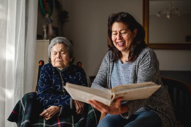 Vecchia donna malata con perdita di memoria seduto in sedia a rotelle. figlia sorridente che tiene un album di foto che prova a ricordare.