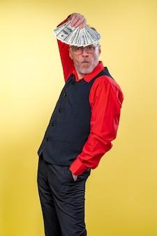 Vecchio sorridente uomo dai capelli grigi in occhiali tenendo ventaglio di dollari sopra la testa in posa di ballo. emozioni umane ed espressioni facciali