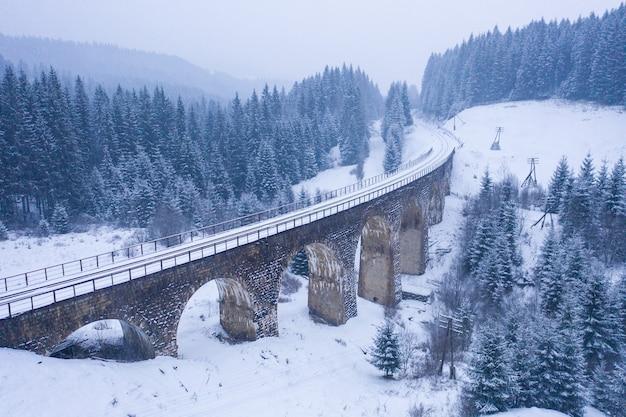 Vecchio viadotto nevoso. vecchio ponte ferroviario coperto di neve in ucraina
