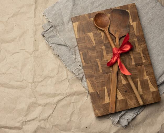 Vecchio cucchiaio e spatola legati con nastro rosso su uno sfondo di carta marrone, vista dall'alto