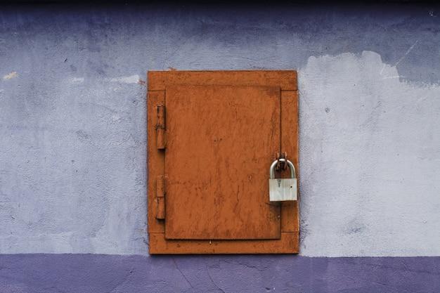 Vecchio portello marrone quadrato con vernice incrinata con la serratura sulla parete viola luminosa.