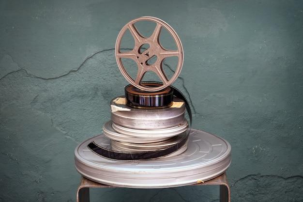Vecchie pellicole cinematografiche vintage impilate di diametri assortiti con una bobina del proiettore